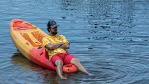 Jonah Stalled, 25 of Saratoga waits for his next kayak rental at the Kayak Shack by dunking his feet in Fish Creek at the north end of Saratoga Lake Thursday June 21, 2018 on the first day of summer in Saratoga Springs, N.Y. (Skip Dickstein/Times Union)
