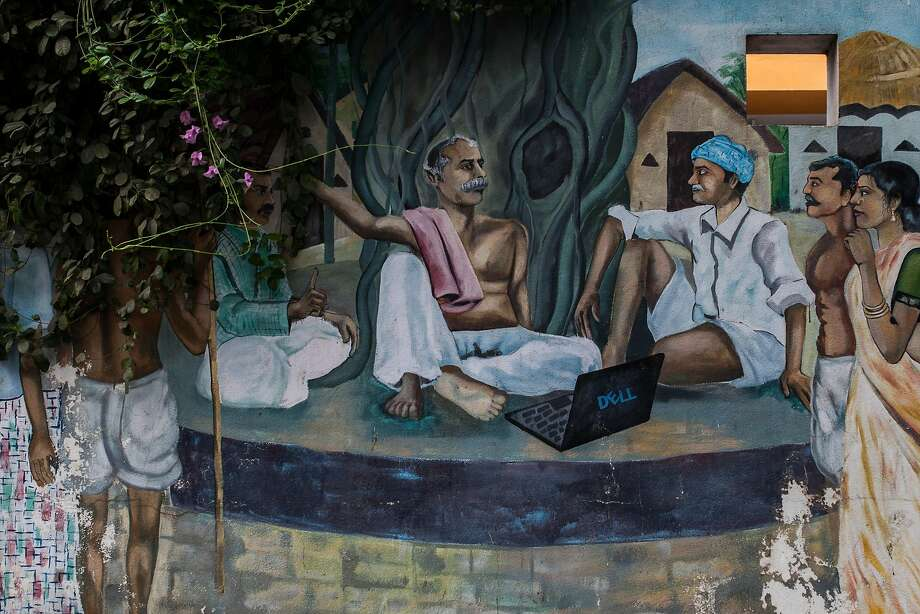 A mural picturing traditional Indian villagers using a laptop is painted on the fence of an engineering company in Hyderabad Information Technology and Engineering Consultancy City. Photo: Bernat Parera / Special To The Chronicle 2016