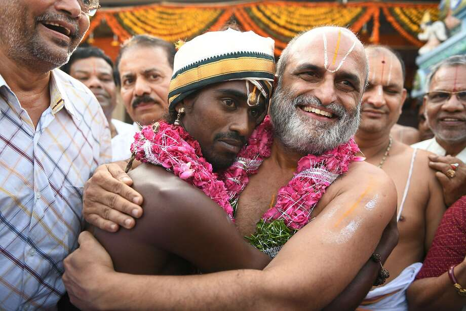 C.S. Rangarajan (right) hugs Aditya Parasri during an April ritual stressing human equality. Rangarajan also serves as a priest at Chilkur Balaji Temple, where people pray for visas. Photo: Noah Seelam / AFP / Getty Images
