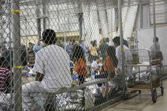 """In this photo provided by U.S. Customs and Border Protection, people who've been taken into custody related to cases of illegal entry into the United States, sit in one of the cages at a facility in McAllen, Texas, Sunday, June 17, 2018. More than 2,300 minors have been separated from their parents since April, when the Trump administration launched its """"zero-tolerance"""" policy that called for prosecuting illegal immigrants and taking their children away. (U.S. Customs and Border Protection's Rio Grande Valley Sector via AP)"""