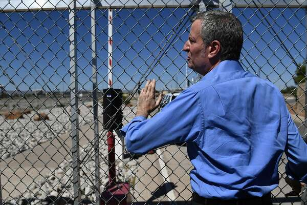 New York mayor Bill de Blasio stands at a fence of the Tornillo Port of Entry near El Paso, Texas, June 21, 2018 during a protest rally by several American mayors against the US administration's family separation policy. President Donald Trump ordered an end to the separation of migrant children from their parents on the US border June 20, 2018, reversing a tough policy under heavy pressure from his fellow Republicans, Democrats and the international community. The spectacular about-face comes after more than 2,300 children were stripped from their parents and adult relatives after illegally crossing the border since May 5 and placed in tent camps and other facilities, with no way to contact their relatives. / AFP PHOTO / Brendan SmialowskiBRENDAN SMIALOWSKI/AFP/Getty Images