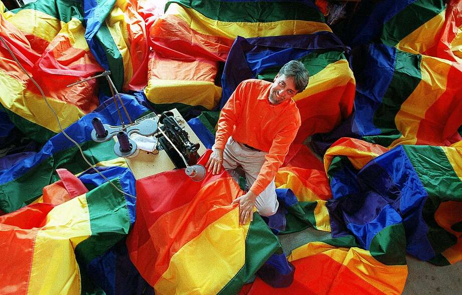 """FILE – This file photo shows """"seam-master"""" Gilbert Baker in his studio amid some of the 500 rainbow flags in 1998. Baker is the original creator of the rainbow flag.  Click ahead to see how the rainbow flag has changed over the 40 years since it was created. >>> Photo: Jerry Telfer / The Chronicle 1998"""