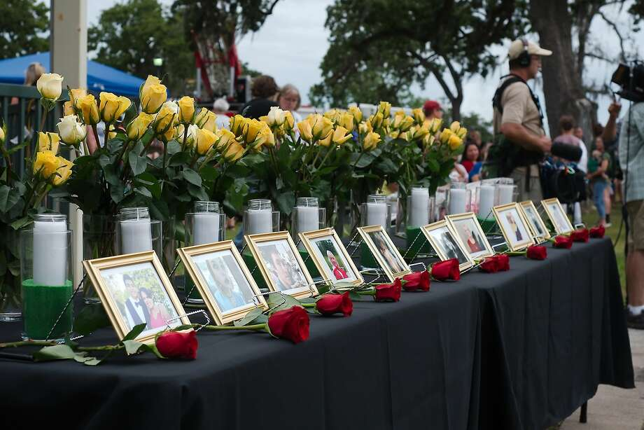 Photos of the victims of the shooting tragedy at Santa Fe High School are on display during a vigil hosted by Moms of Galveston County at Walter Hall Park in League City Sunday, May 20. Photo: Kirk Sides, Houston Chronicle