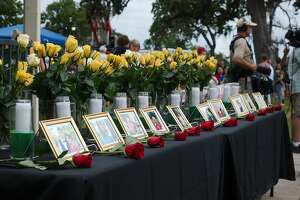 Photos of the victims of the shooting tragedy at Santa Fe High School are on display during a vigil hosted by Moms of Galveston County at Walter Hall Park in League City Sunday, May 20.