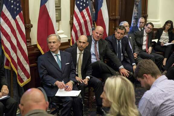 Gov. Greg Abbott of Texas, left, listens at a roundtable in Austin on May 24, 2018 with students who survived the Santa Fe High School mass shooting. Two weeks later, Abbott has proposed spending more than $100 million to hire more armed guards for schools, expanding programs to identify students at risk of engaging in mass violence and limiting the number of school entrances and exits.