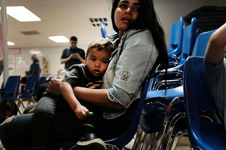 MCALLEN, TX - JUNE 21: A woman who idendtified herself as Jennifer sits with her son Jaydan at the Catholic Charities Humanitarian Respite Center after recently crossing the U.S., Mexico border on June 21, 2018 in McAllen, Texas. Once families and individuals are released from Customs and Border Protection to continue their legal process, they are brought to the center to rest, clean up, enjoy a meal and get guidance to their next destination. Before Trump signed an executive order yesterday that the administration says halts the practice of separating families seeking asylum, more than 2,300 immigrant children had been separated from their parents in the  zero-tolerance policy for border crossers. (Photo by Spencer Platt/Getty Images)