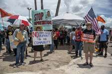 Demonstrators hold signs outside of a Border Patrol station in McAllen on Sunday. They were protesting President Donald Trump's policy of separating immigrant children from parents who illegally cross the Mexican border.
