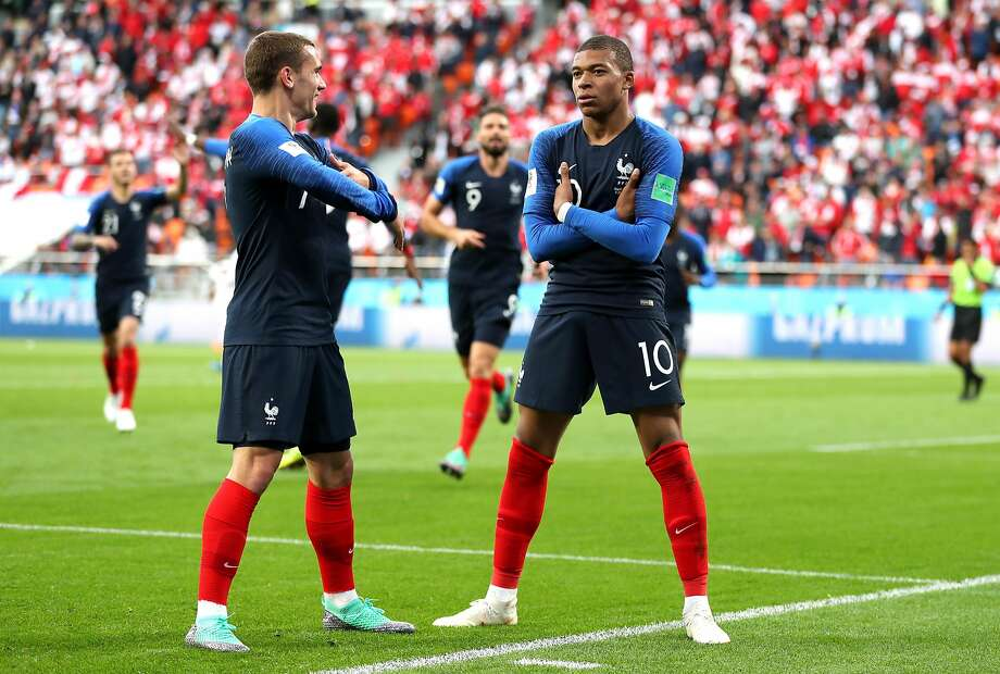 Kylian Mbappe (right) and Antoine Griezmann begin a celebration of Mbappe's goal by folding their arms. Photo: Catherine Ivill / Getty Images
