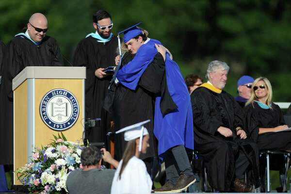 Hunter Hazelton hugs principal Ellen Dunn after receiving his diploma during the Darien High School Class of 2018 Commencement ceremony on the school's football field in Darien, Conn. on Thursday, June 21, 2018.