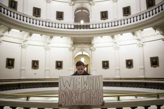 "A protester holds a sign that reads ""We will overcome"" in the rotunda of the state Capitol shortly after the Electoral College cast their vote in Austin on Dec. 19, 2016. The ballots of three dozen Texas presidential electors put Donald Trump over the 270 electoral votes needed to formally win the White House."