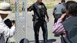A Department of Homeland Security agent closes a gate Thursday at the Port of Entry facility in Fabens, near El Paso,  where tent shelters are being used to house separated family members. President Donald Trump's order ending the policy of separating immigrant families at the border leaves a host of unanswered questions, including what happens to the more than 2,300 children already taken from their parents and where the government will house all the newly detained migrants in a system already bursting at the seams. (AP Photo/Matt York)