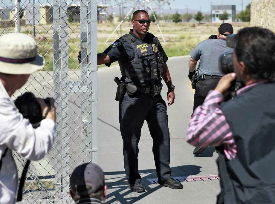 A Department of Homeland Security agent closes a gate Thursday at the Port of Entry facility in Fabens, near El Paso,  where tent shelters are being used to house separated family members. President Donald Trump's order ending the policy of separating immigrant families at the border leaves a host of unanswered questions, including what happens to the more than 2,300 children already taken from their parents and where the government will house all the newly detained migrants in a system already bursting at the seams. (AP Photo/Matt York) Photo: Matt York /Associated Press / Copyright 2018 The Associated Press. All rights reserved.