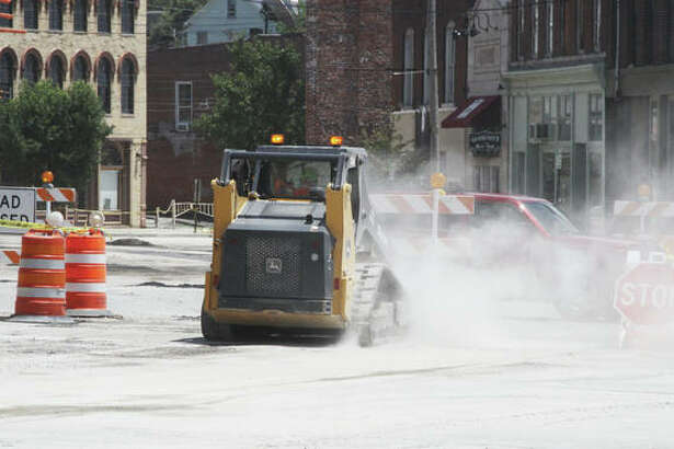 A worker from contractor J.P. Burns Excavating Inc. of Plainview, Illinois, sweeps off cement dust Thursday afternoon from East Broadway at Henry Street at the westernmost portion of the sewer replacement project that started May 7 and ran east to Vine Street.