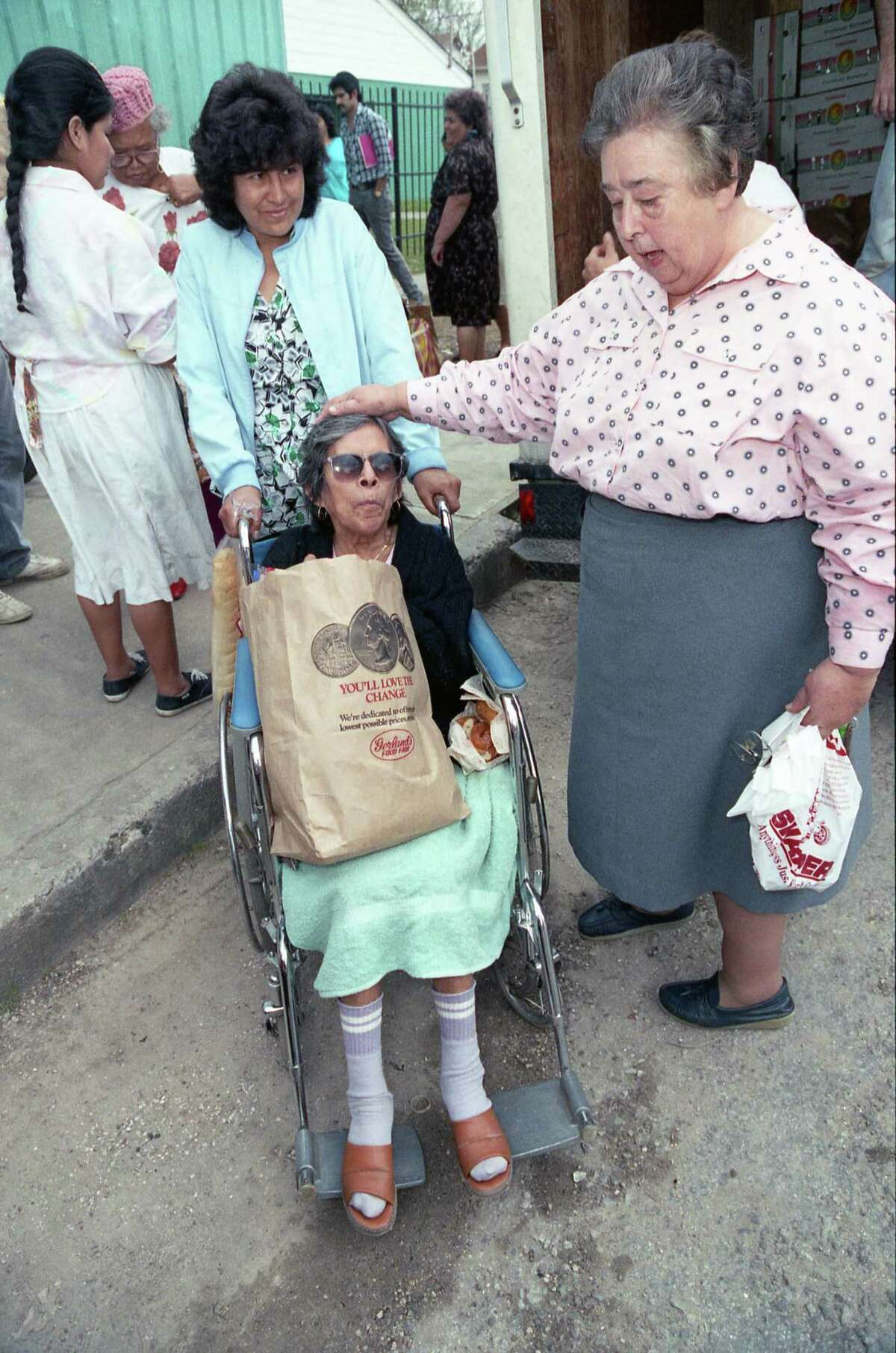 Mildred McWhorter, assisted by Carmen Santillan. extends a comforting hand to Rosa Martinez, in wheelchair, after Martinez received a donated bag of groceries from the Fletcher Mission Center. The center purchases food from the Houston Area Food Bank, which is supported by grocers, including Gerland's.