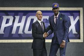 Arizona's Deandre Ayton, right, poses with NBA Commissioner Adam Silver after he was picked first overall by the Phoenix Suns during the NBA basketball draft in New York, Thursday, June 21, 2018.