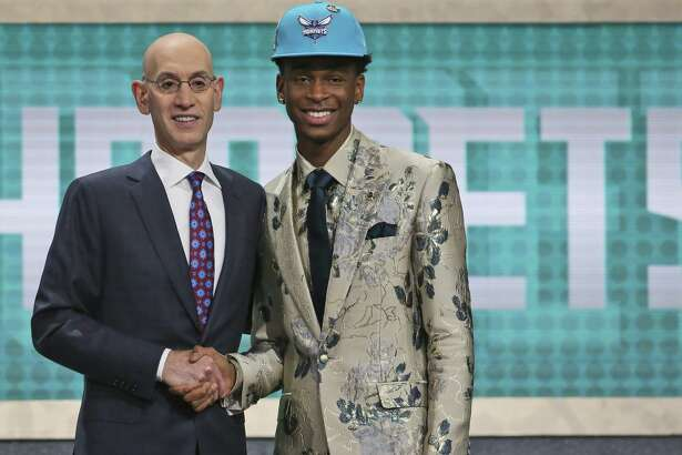 Kentucky's Shai Gilgeous-Alexander, right, poses with NBA Commissioner Adam Silver after he was picked 11th overall by the Charlotte Hornets during the NBA basketball draft in New York, Thursday, June 21, 2018. (AP Photo/Kevin Hagen)