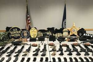 Shown are the 21 rifles and other tactical equipment federal authorities seized on Tuesday from a downtown parking lot. No arrest has been made.