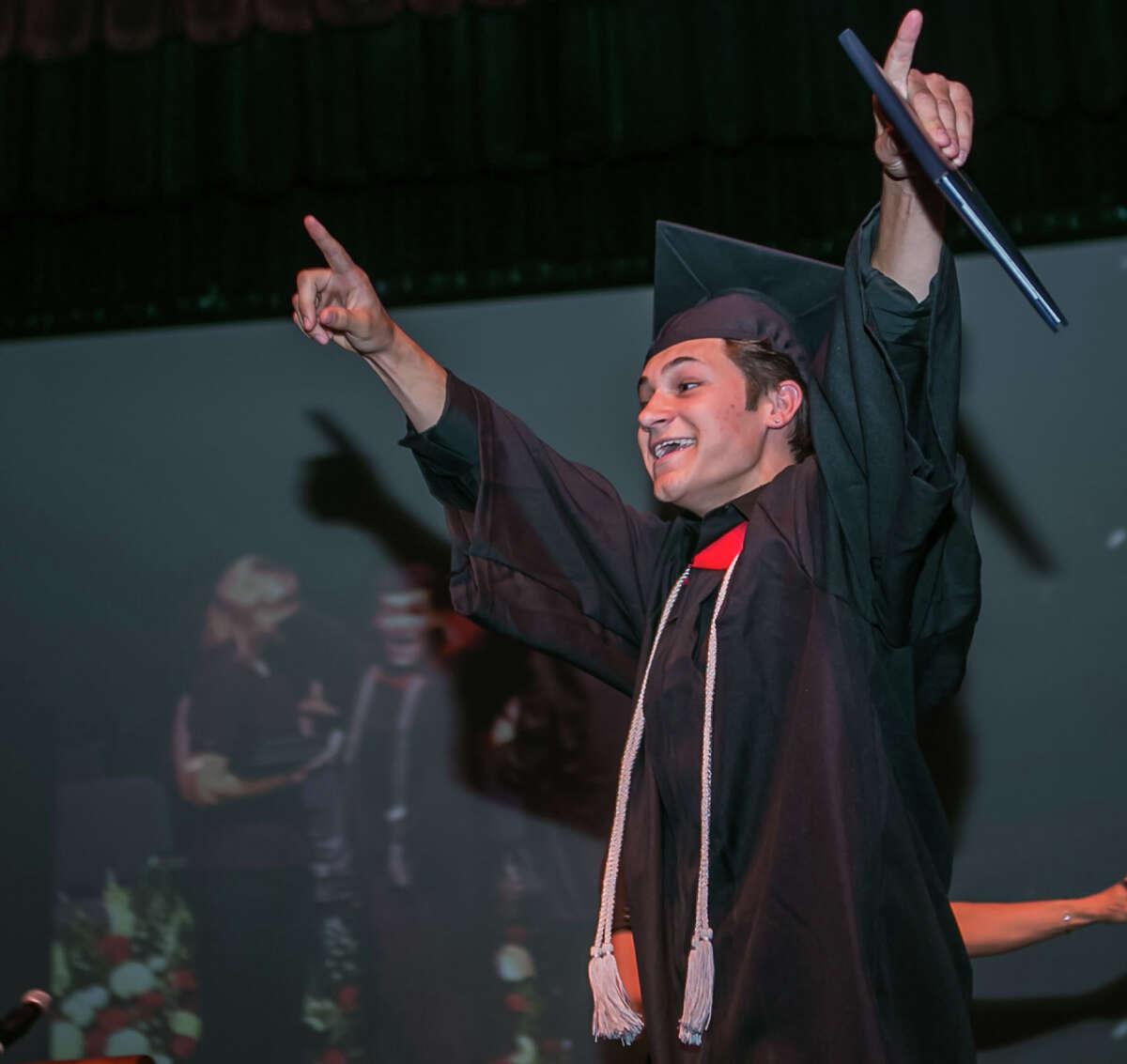 (John Vanacore/For Hearst Connecticut Media) Platt Tech Graduate William Esposito celebrates after receiving his diploma Thursday evening.