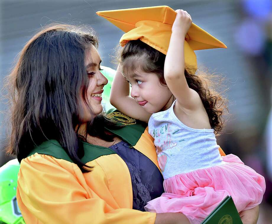 Emily Parra, a member of the class of 2018 at Hamden High School lets her 2-year old sister Isabella try on her mortar board following commencement exercises at Joe Bruno Field in Hamden, Thursday, June 21, 2018. Photo: Catherine Avalone, Hearst Connecticut Media / New Haven Register