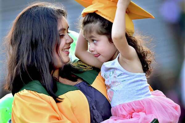 Emily Parra, a member of the class of 2018 at Hamden High School lets her 2-year old sister Isabella try on her mortar board following commencement exercises at Joe Bruno Field in Hamden, Thursday, June 21, 2018.