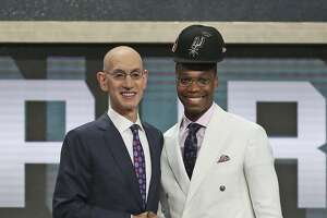 Miami's Lonnie Walker IV, right, poses with NBA Commissioner Adam Silver after he was picked 18th overall by the San Antonio Spurs during the NBA basketball draft in New York, Thursday, June 21, 2018. (AP Photo/Kevin Hagen)