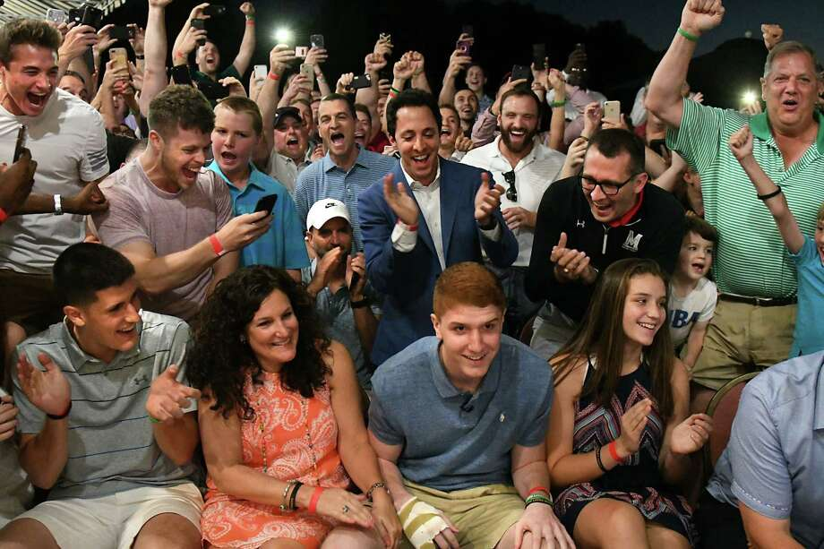 Friends and family react after hearing that Shenendehowa graduate Kevin Huerter, front row center, is picked by the Atlanta Hawks in the first round of the 2018 NBA Draft, 19th overall, at the Edison Club on Thursday, June 21, 2018 in Rexford, N.Y. (Lori Van Buren/Times Union) Photo: Lori Van Buren, Albany Times Union / 20044181A