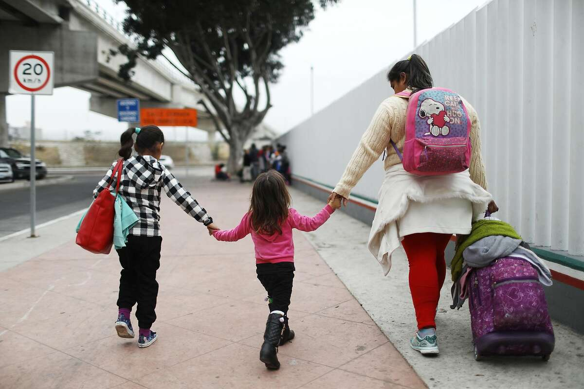 TIJUANA, MEXICO - JUNE 21: A migrant mother walks with her two daughters on their way to the port of entry to ask for asylum in the U.S. on June 21, 2018 in Tijuana, Mexico. The mother, who did not wish to give their names, said they were fleeing their hometown near the Pacific coast of Mexico after suffering a violent carjacking of her taxicab. The Trump Administration's controversial zero tolerance immigration policy led to an increase in the number of migrant children who have been separated from their families at the southern U.S. border. U.S. Attorney General Jeff Sessions has added that domestic and gang violence in immigrants' country of origin would no longer qualify them for political asylum status. (Photo by Mario Tama/Getty Images)
