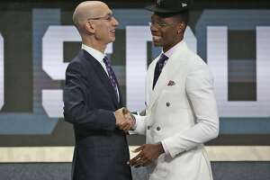 Miami's Lonnie Walker IV, right, shakes hands with NBA Commissioner Adam Silver after he was picked 18th overall by the San Antonio Spurs during the NBA basketball draft in New York, Thursday, June 21, 2018. (AP Photo/Kevin Hagen)
