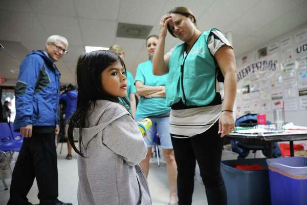 MCALLEN, TX - JUNE 21: Jenquel, who recently crossed the U.S., Mexico border with her mother and siblings, speaks with volunteers at the Catholic Charities Humanitarian Respite Center on June 21, 2018 in McAllen, Texas. Once families and individuals are released from Customs and Border Protection to continue their legal process, they are brought to the center to rest, clean up, enjoy a meal and get guidance to their next destination. Before Trump signed an executive order yesterday that the administration says halts the practice of separating families seeking asylum, more than 2,300 immigrant children had been separated from their parents in the  zero-tolerance policy for border crossers. (Photo by Spencer Platt/Getty Images)