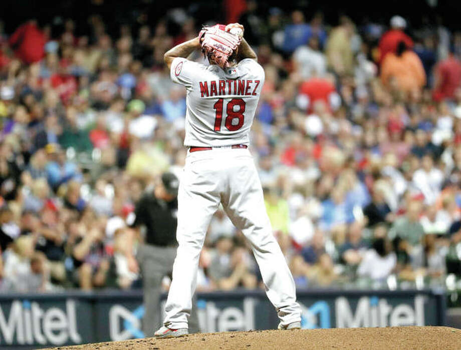 Cardinals starting pitcher Carlos Martinez reacts after throwing a wild pitch to allow a run in the third inning of Thursday night's game against the Brewers at Miller Park in Milwaukee.
