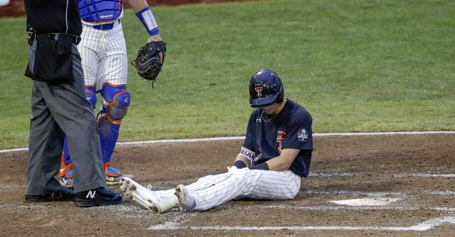 Texas Tech's Gabe Holt falls down while swinging during at-bat with the bases loaded as Florida catcher Brady Smith stands next to home plate umpire Chris Coskey during the second inning of an NCAA College World Series baseball elimination game in Omaha, Neb., Thursday, June 21, 2018. (AP Photo/Nati Harnik) Photo: Nati Harnik/Associated Press