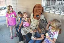 """McGruff the Crime Dog has returned to active duty after a four-year hiatus. He appeared Thursday at Charlie's Coffee & Cones at 115 W. Lafayette Ave., where the public had a chance to talk with him and Jacksonville police officers during the """"Cone with a Cop"""" event. Visiting with McGruff are Khrystina Warcup, 9, (from left) Kaedyn Jourdan, 10, Melindy Jourdan, 9, Marley Warcup, 7, and Kaya Warcup, 6."""