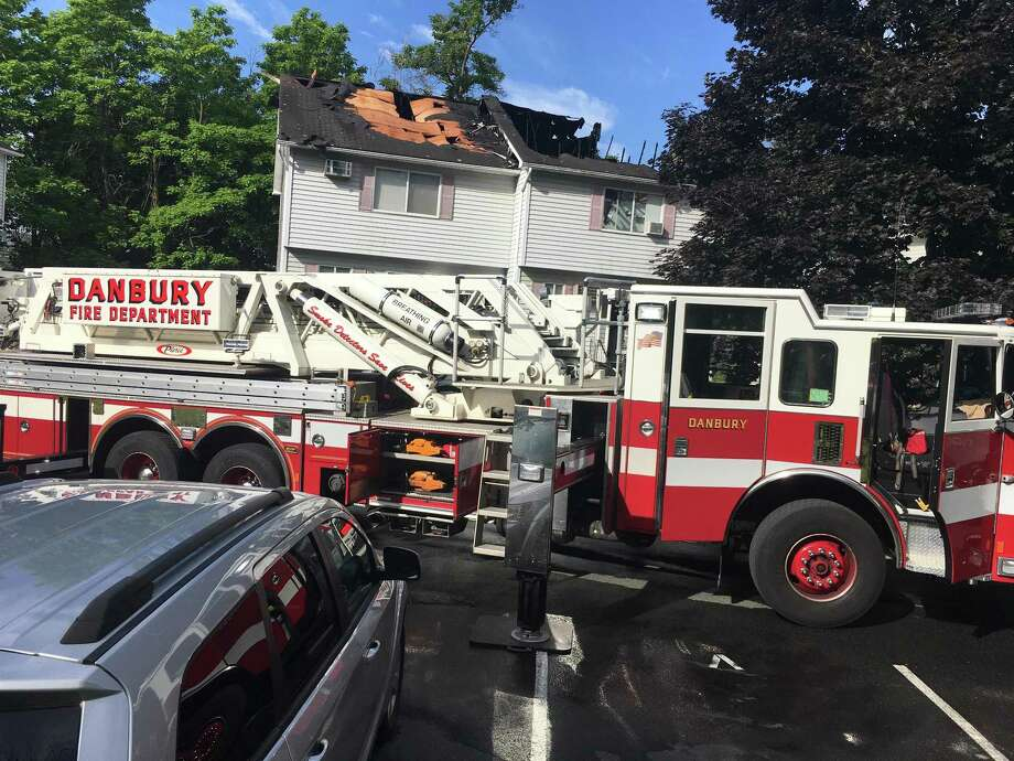 Four condominiums were heavily damaged in a fire that broke out around 6:30 a.m. Friday, June 22, 2018. All residents of the condominiums were able to safety escape. One firefighter was taken to Danbury Hospital for observation. When firefighters arrived at the condo complex at Triangle and Cook streets, they encountered heavy fire and smoke coming from one of the buildings. Photo: Dirk Perrefort /Hearst Connecticut Media
