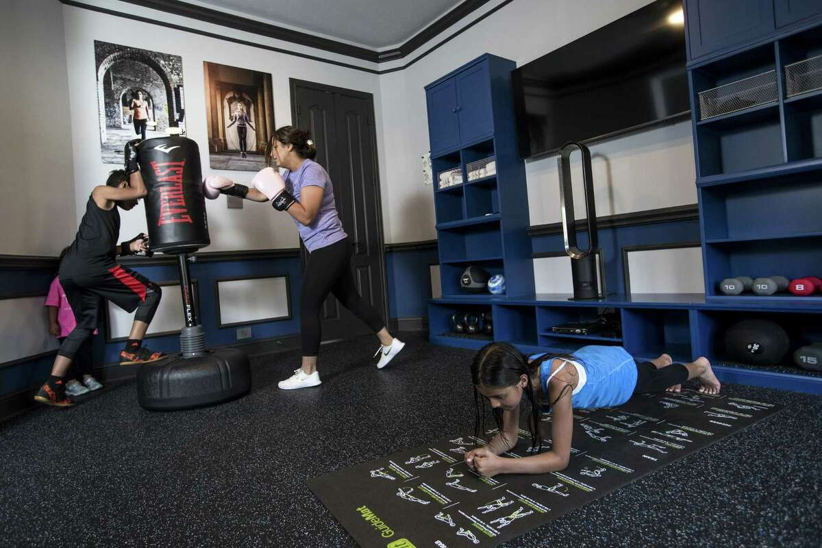 Neda Malkani works out with her son, Armaan, 11, and daughter, Meher, 9, in her excercise room, that was once a formal dining room at her home, on Friday, June 1, 2018, in Humble. ( Brett Coomer / Houston Chronicle )
