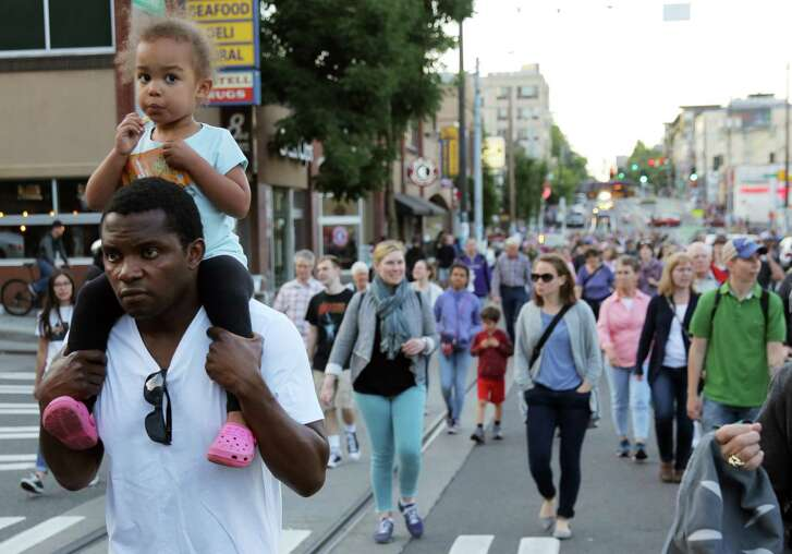 A crowd of more than 1,000 people, including many clergy and parishioners, marches down Broadway from St. Mark's Episcopal Cathedral to St. James Catholic Cathedral on Thursday night, in a procession for families imprisoned and separated at the border, Thursday, June 22, 2018. (Genna Martin, seattlepi.com)