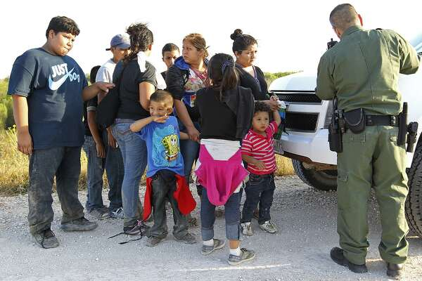Immigrant adults and children huddle as a U.S. Border Patrol agent questions them near Anzalduas Park, southwest of McAllen, Texas, Wednesday, June 11, 2014. Soon after, to avoid media attention, the agents hustled them into a transportation van. The group of 13 walked up to the agents. A wave of Central American adults with children and unaccompanied minors has overwhelmed U.S. Immigration and Customs detention centers. Immigration officials release some of them on their own recognizance after undergoing processing.
