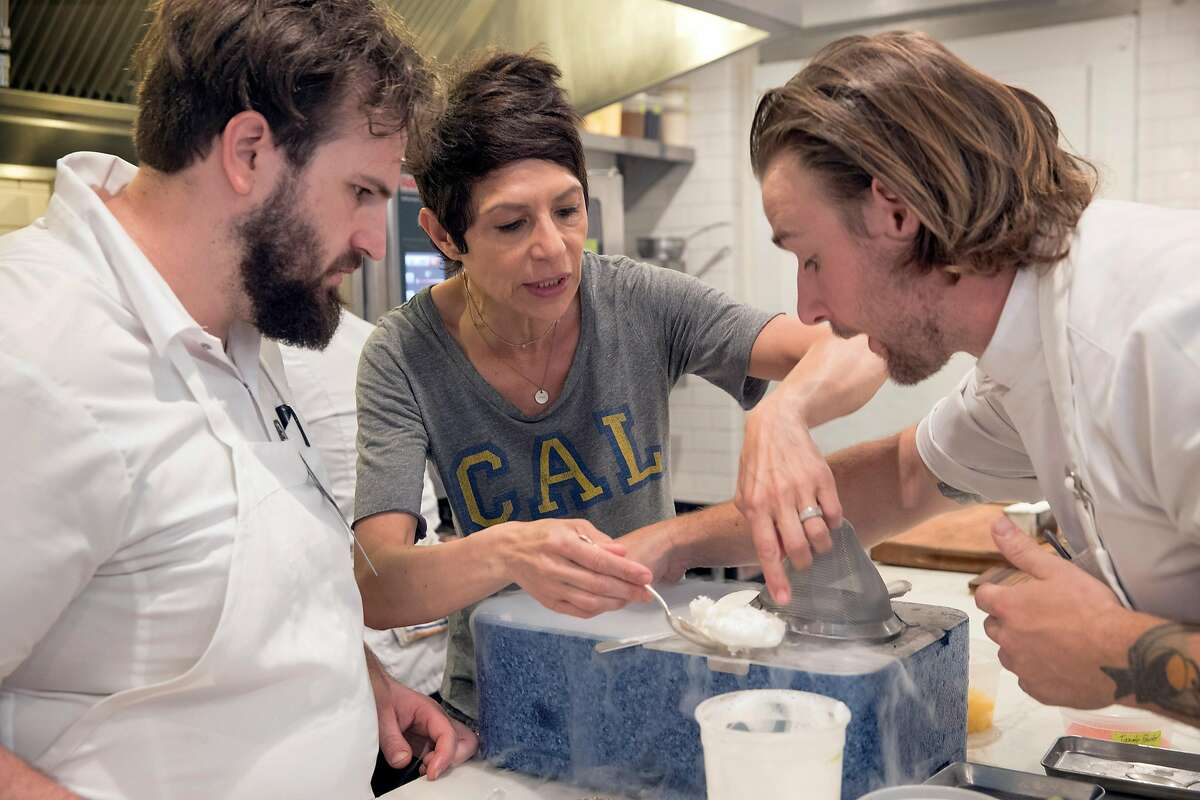 FILE - Chef Dominique Crenn, center, checks on a recipe using liquid nitrogen at Atelier Crenn in San Francisco, Calif., on Wednesday, June 13, 2018.