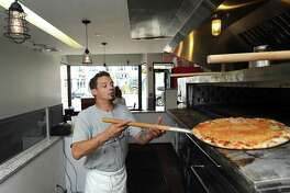 Chef Mike Mendoza removes a fresh pizza from the oven inside New Haven-style pizzeria Teena's Apizza, at 245 Main St., in downtown Stamford, Conn., on Monday, June 18, 2018.