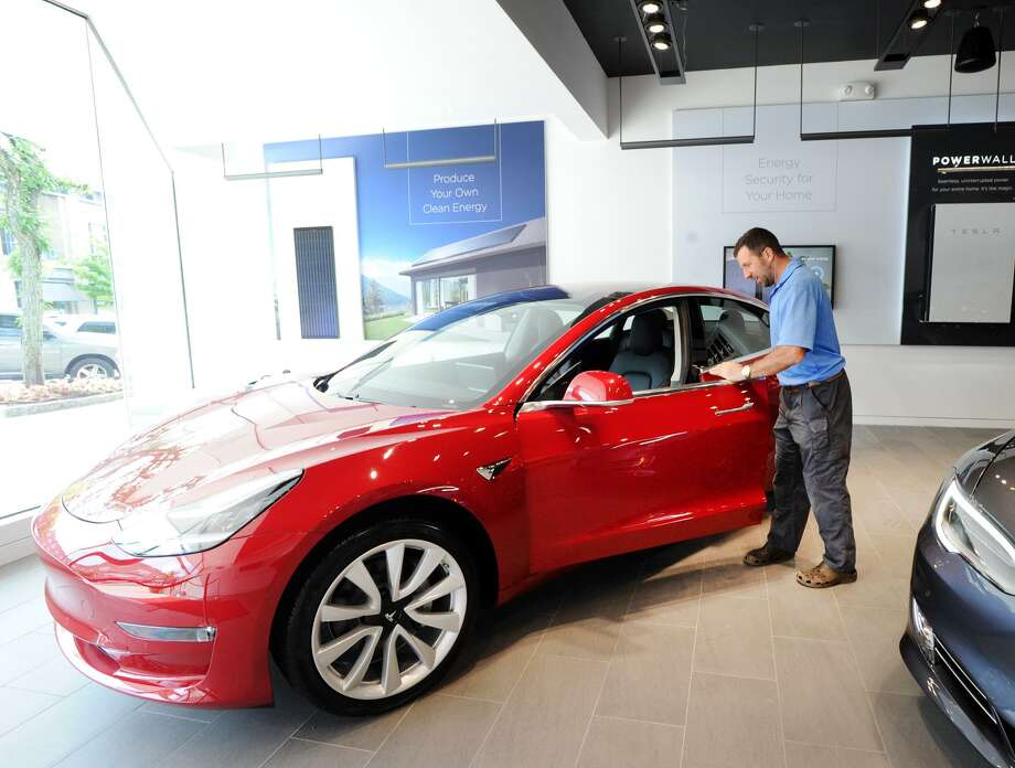 Dom Vivona of Old Greenwich inspects a Tesla Model 3 on display inside the Tesla Gallery at 340 Greenwich Ave., Greenwich, Conn., Friday, June 22, 2018. Vivona said his name is on the waiting-list to acquire a 4-wheel drive version of the vehicle. According to Car & Driver Magazine, the sale price for the electric rechargable battery-powered Model 3 is $36,000, it does 0- 60 mph in 5.1 seconds with a top speed of 141 mph and the rear-wheel-drive models travel about 220 miles on a single charge. Photo: Bob Luckey Jr. / Hearst Connecticut Media / Greenwich Time