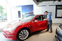 Dom Vivona of Old Greenwich inspects a Tesla Model 3 on display inside the Tesla Gallery at 340 Greenwich Ave., Greenwich, Conn., Friday, June 22, 2018. Vivona said his name is on the waiting-list to acquire a 4-wheel drive version of the vehicle. According to Car & Driver Magazine, the sale price for the electric rechargable battery-powered Model 3 is $36,000, it does 0- 60 mph in 5.1 seconds with a top speed of 141 mph and the rear-wheel-drive models travel about 220 miles on a single charge.