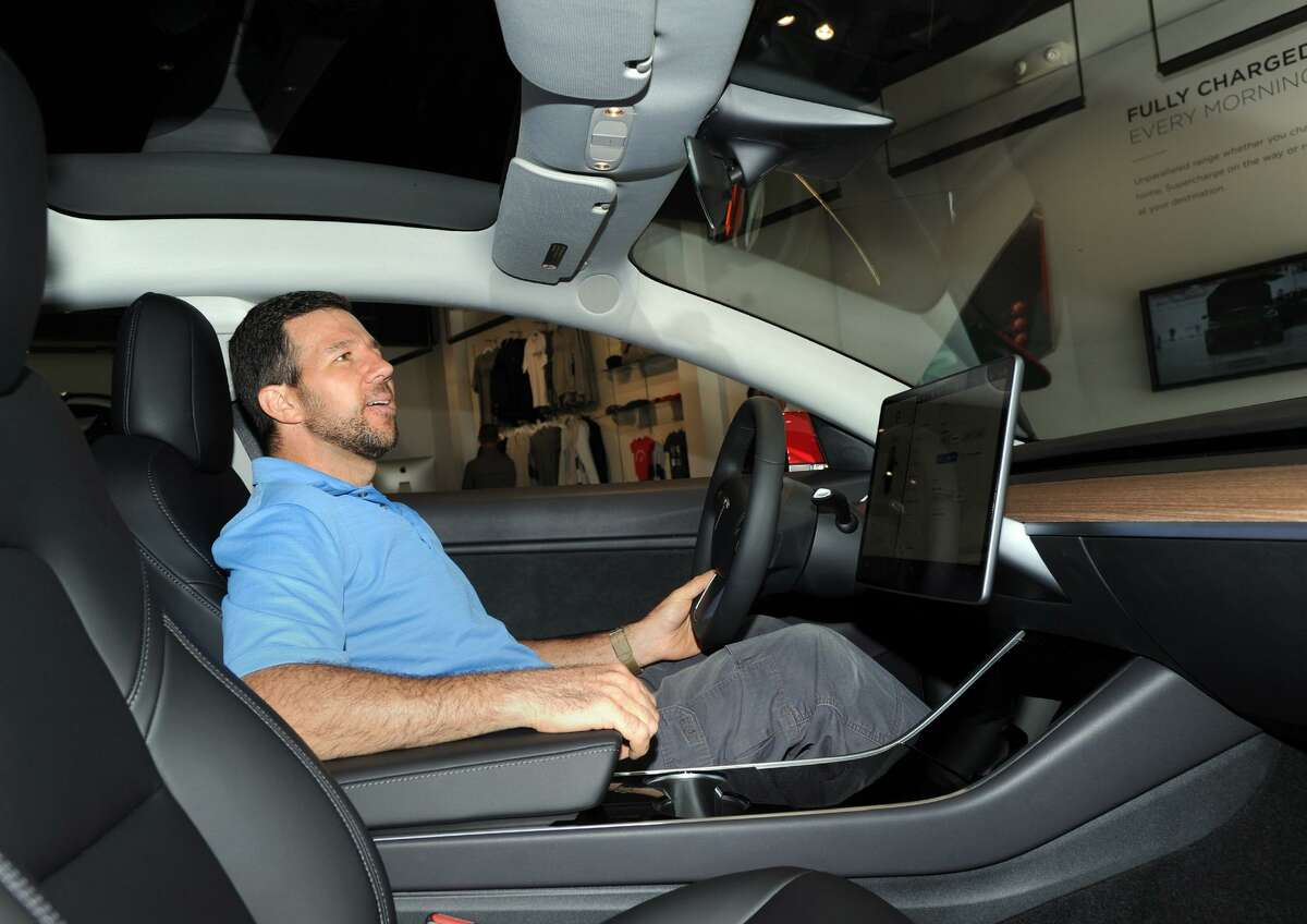 Dom Vivona of Old Greenwich sits behind the wheel of a Tesla Model 3 on display inside the Tesla Gallery at 340 Greenwich Ave., Greenwich, Conn., Friday, June 22, 2018. Vivona said his name is on the waiting-list to acquire a 4-wheel drive version of the vehicle. According to Car & Driver Magazine, the sale price for the electric rechargable battery-powered Model 3 is $36,000, it does 0- 60 mph in 5.1 seconds with a top speed of 141 mph and the rear-wheel-drive models travel about 220 miles on a single charge.