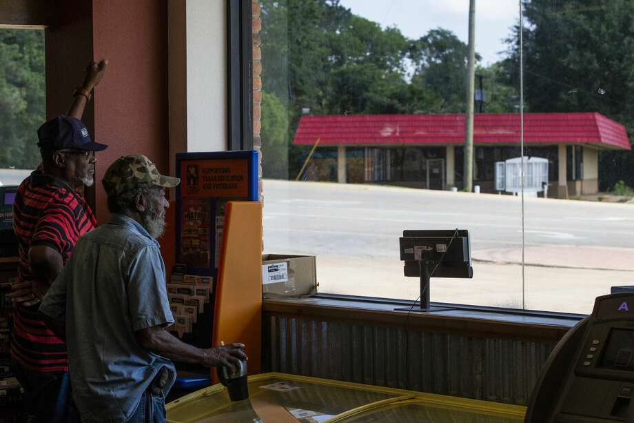 James Watts, left, and Rooster Davis, right, look out toward the old Dairy Queen across the street from the R&D convenience store in San Augustine. Some people in town blame the influx of other fast food chains for the closing of the Dairy Queen. Photo: Michael Ciaglo