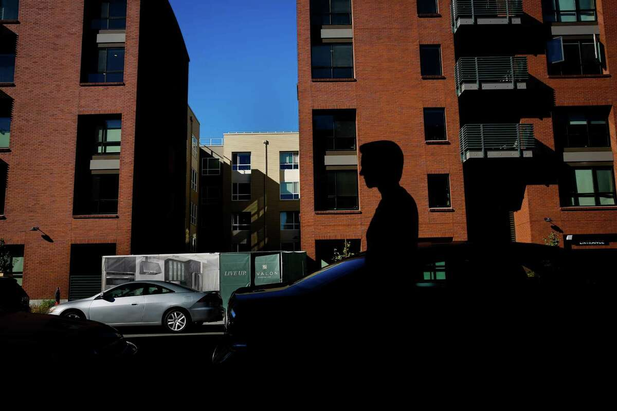 A man walks by the Avalon apartments in the Dogpatch neighborhood of San Francisco.