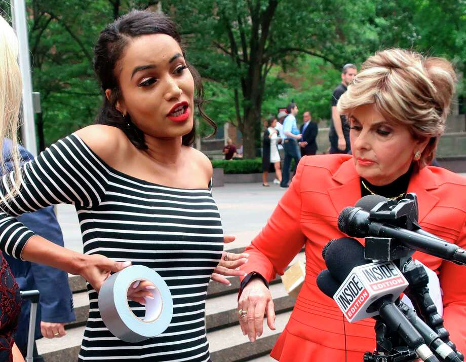 PHOTOS: Former Texans cheerleaders involved in the lawsuit against the team Former Houston Texans cheerleader Angelina Rosa demonstrates during a news conference outside NFL headquarters in New York, Friday, June 22, 2018,  how she says she was forced to use duct tape to make her look skinnier during a game last year. Her attorney Gloria Allred, right, looks on. Rosa joins five other Texans cheerleaders in a lawsuit alleging the team failed to fully compensate them as required by law and subjected them to hostile work environment in which they were harassed, intimidated and forced to live in fear. (AP Photo/Ted Shaffrey) Photo: Associated Press / Copyright 2018 The Associated Press. All rights reserved.