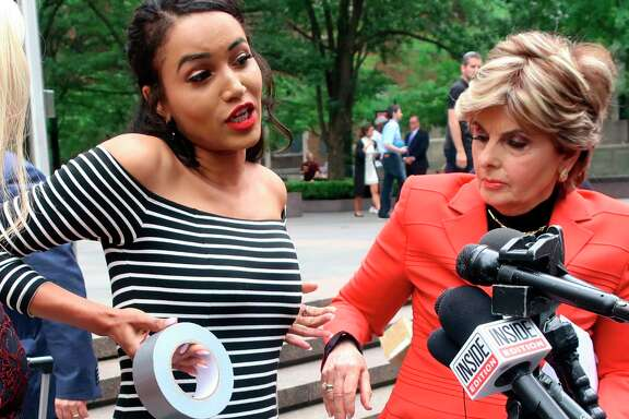 Former Houston Texans cheerleader Angelina Rosa demonstrates during a news conference outside NFL headquarters in New York, Friday, June 22, 2018,  how she says she was forced to use duct tape to make her look skinnier during a game last year. Her attorney Gloria Allred, right, looks on. Rosa joins five other Texans cheerleaders in a lawsuit alleging the team failed to fully compensate them as required by law and subjected them to hostile work environment in which they were harassed, intimidated and forced to live in fear. (AP Photo/Ted Shaffrey)