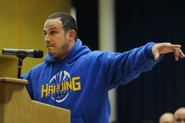 Harding High School football and wrestling coach Eddie Santiago points to his players as he addresses a public hearing over budget cuts before the Bridgeport Board of Education at Geraldine Johnson School in Bridgeport, Conn. on Monday, April 30, 2018.