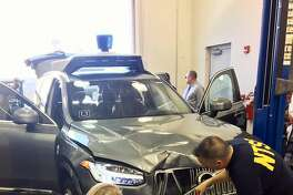 FILE - In this March 20, 2018 file photo provided by the National Transportation Safety Board, investigators examine a driverless Uber SUV that fatally struck a woman in Tempe, Ariz.  An Arizona police report says the human backup driver the Uber autonomous SUV was streaming a television show on Hulu just before the vehicle struck and killed a pedestrian in March. The Arizona Republic reported that the driver was watching �The Voice,� a television musical talent show. The newspaper received the more than 300-page report from Tempe police on Thursday, June 21.  (National Transportation Safety Board via AP)