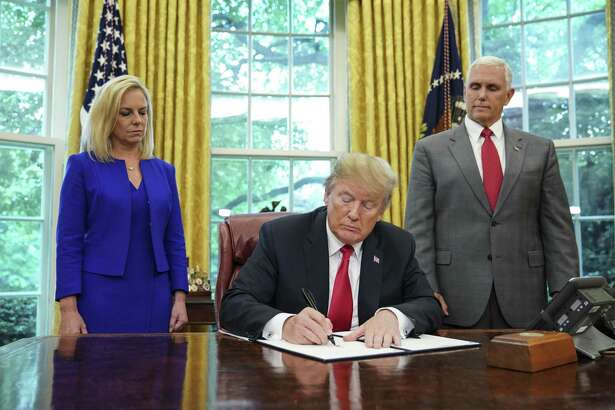 Watched by Homeland Security Secretary Kirstjen Nielsen, left, and Vice President Mike Pence, President Donald Trump signs an executive order Wednesday aimed at putting an end to the controversial separation of migrant families at the border, reversing a harsh practice that had earned international scorn.