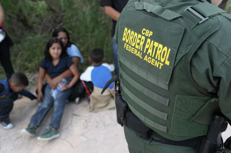 """Central American asylum seekers wait as U.S. Border Patrol agents take them into custody on June 12 near McAllen, Texas. The families were then sent to a U.S. Customs and Border Protection (CBP) processing center for possible separation. U.S. border authorities are executing the Trump administration's """"zero tolerance"""" policy towards undocumented immigrants. U.S. Attorney General Jeff Sessions also said that domestic and gang violence in immigrants' country of origin would no longer qualify them for political asylum status. Photo: John Moore /Getty Images / 2018 Getty Images"""