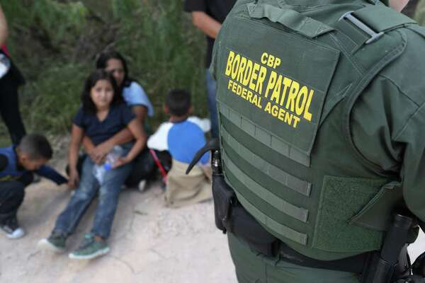 "Central American asylum seekers wait as U.S. Border Patrol agents take them into custody on June 12 near McAllen, Texas. The families were then sent to a U.S. Customs and Border Protection (CBP) processing center for possible separation. U.S. border authorities are executing the Trump administration's ""zero tolerance"" policy towards undocumented immigrants. U.S. Attorney General Jeff Sessions also said that domestic and gang violence in immigrants' country of origin would no longer qualify them for political asylum status."